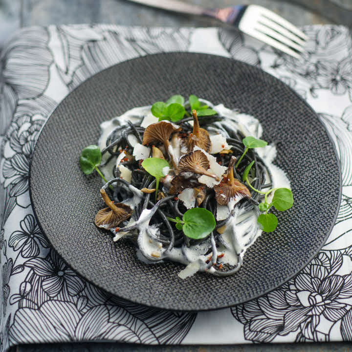 Recette all'italiana : spaghetti noirs aux champignons, tomates séchées et crème au parmesan.