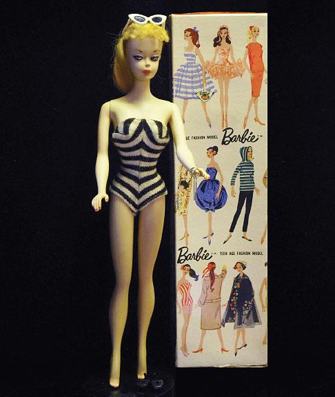 Barbie vintage avec une planche de vêtements créés pour elle.